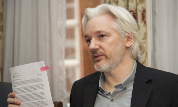 Julian Assange muestra un documento